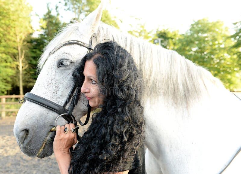 Vrouw met wit paard stock fotografie