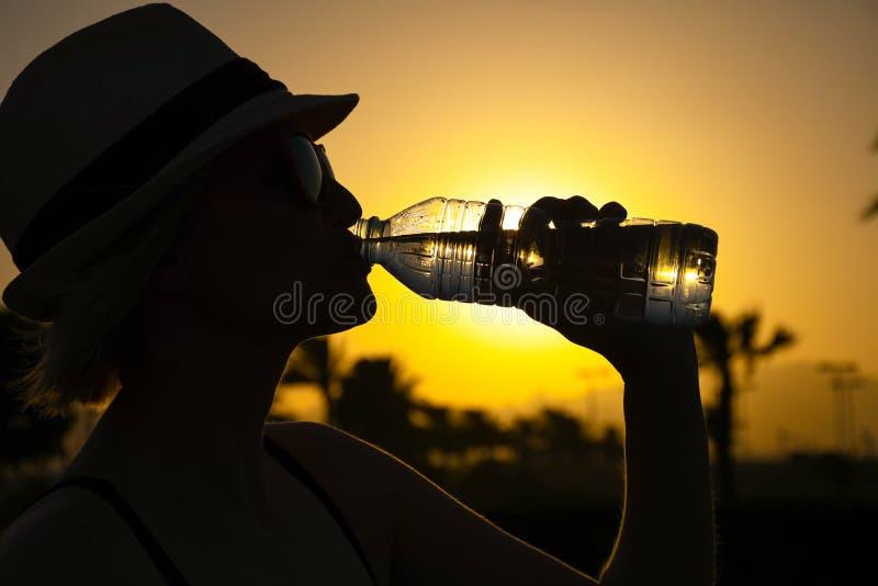 Vrouw met witte hoed en roze zonnebril met aardige bezinning van palmen en zonsondergang die vers zuiver water drinken royalty-vrije stock foto