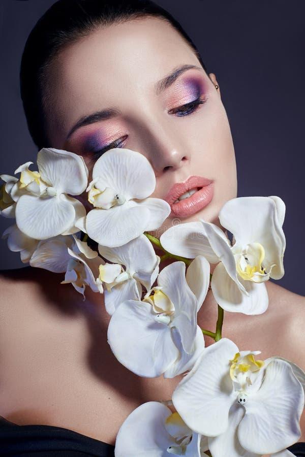 Vrouw met witte Orchidee dichtbij gezichtsmeisje met mooie heldere mak stock afbeelding
