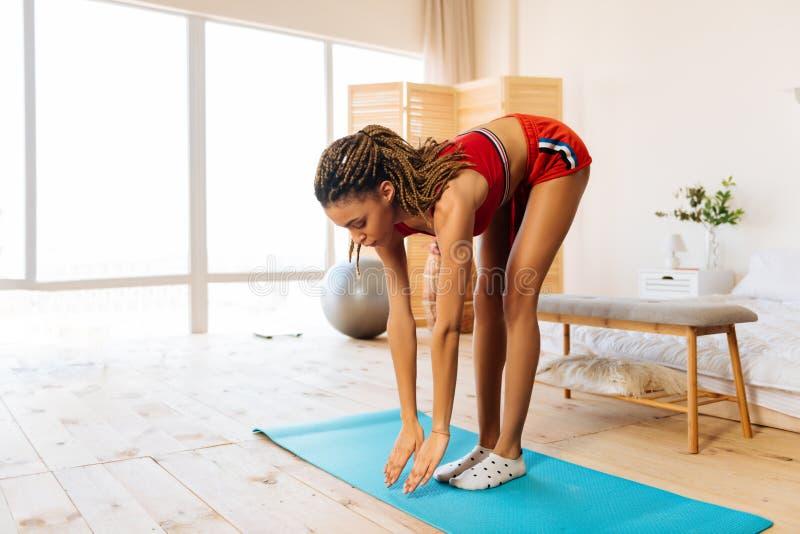 Vrouw met zich het aardige lichaam uitrekken die zich op blauwe sportmat bevinden stock foto's