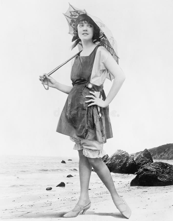 Vrouw met zonparaplu en badpak bij het strand (Alle afgeschilderde personen leven niet langer en geen landgoed bestaat leverancie royalty-vrije stock fotografie