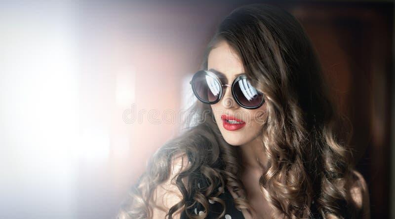 Vrouw met zwarte zonnebril en lang krullend haar Mooi vrouwenportret De foto van de manierkunst van jong model met zonnebril royalty-vrije stock afbeelding