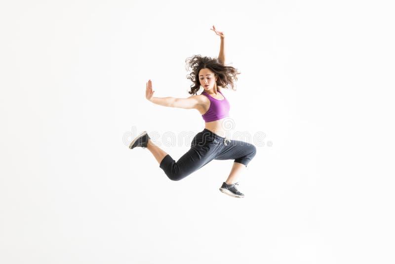 Vrouw in Midair het Praktizeren Balletbewegingen tegen Witte Achtergrond stock foto