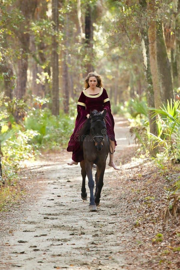 Vrouw in middeleeuwse kledings berijdende horseback stock afbeelding