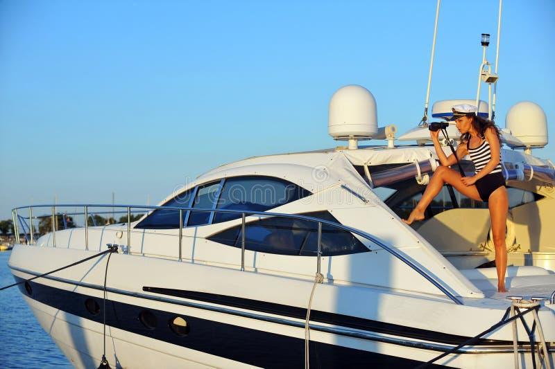 Vrouw in modieus zwempak en kapiteinshoed op privé motorboot op vakantie stock afbeeldingen