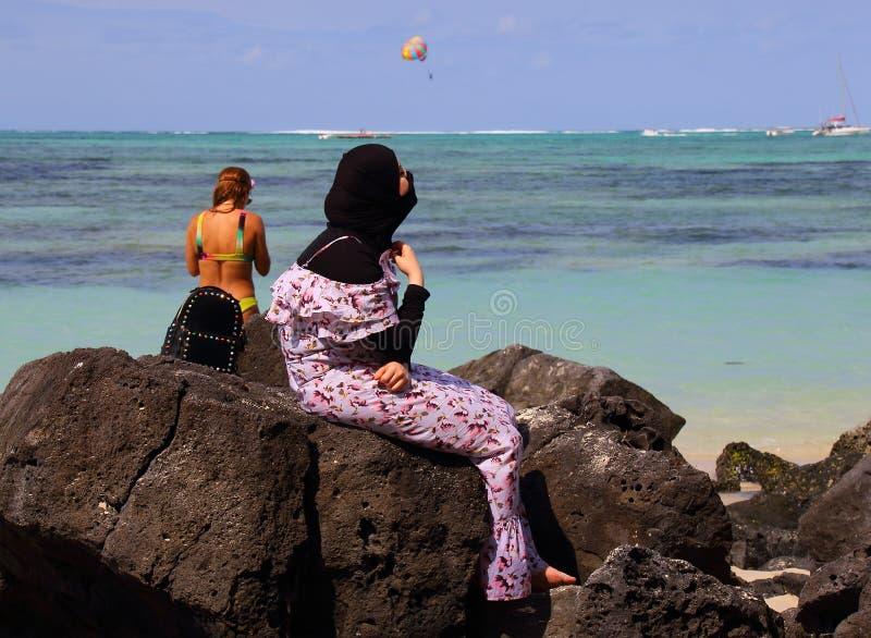 Vrouw in Moslimkleding op het strand stock foto's