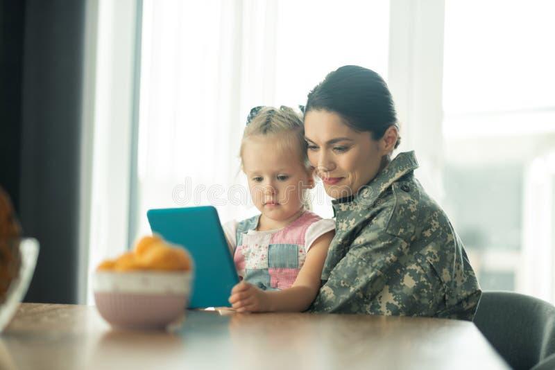 Vrouw na legerdienst gelukkig voelen koesterend haar kind stock afbeeldingen