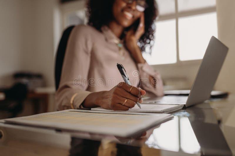 Vrouw nota's maken die thuis werkend aan laptop stock foto