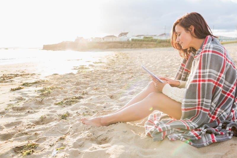 Vrouw omvat met deken die tabletpc met behulp van bij strand royalty-vrije stock foto's
