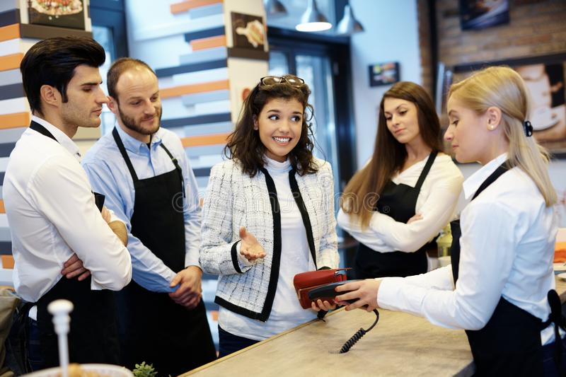 Vrouw onbekwaam aan loonsrekening in cafetaria stock afbeeldingen