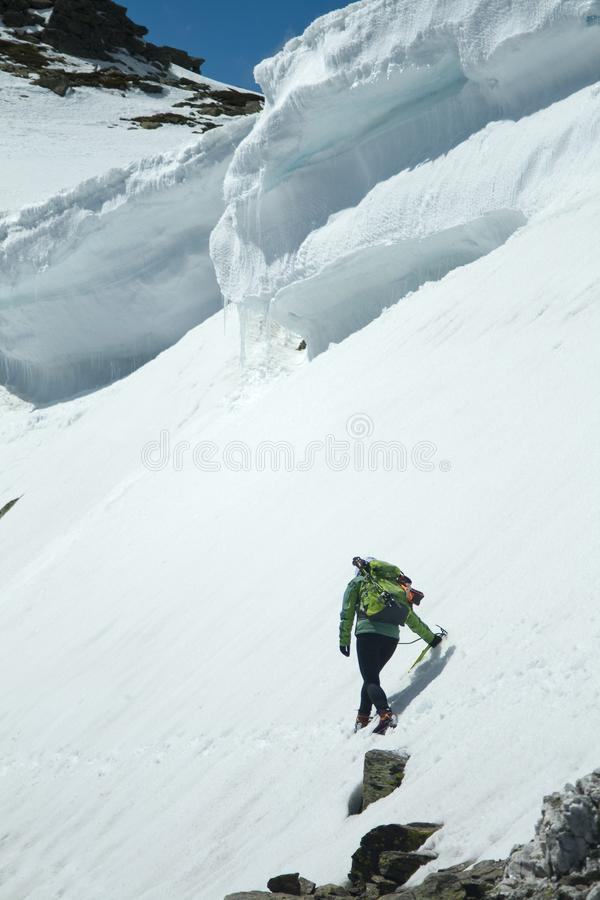 Vrouw onder een sneeuwkroonlijst in een berg op een zonnige dag stock fotografie