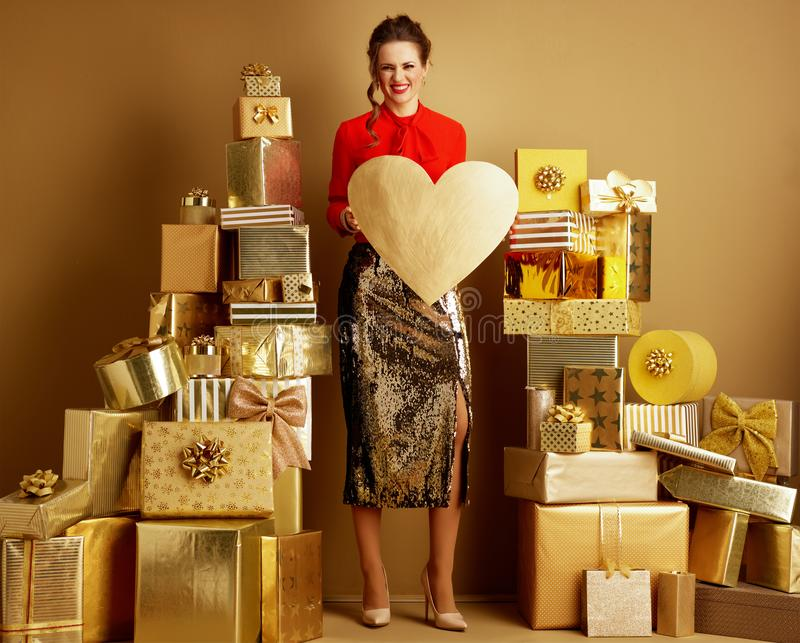 Vrouw onder 2 stapels van gouden giften die gouden hart tonen royalty-vrije stock foto
