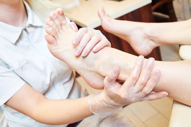 Vrouw onder voetmassage vóór pedicureprocedure in schoonheidssalon stock fotografie