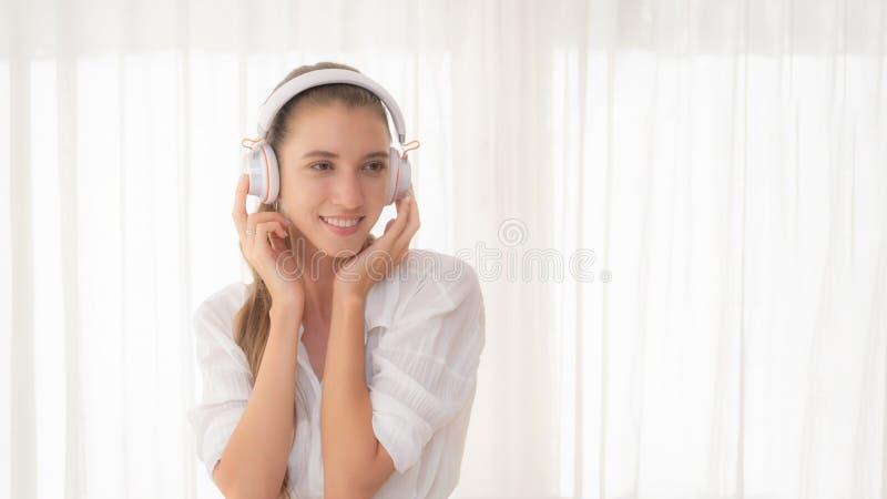 Vrouw ontspannen die aan muziek met hoofdtelefoons luisteren stock afbeelding