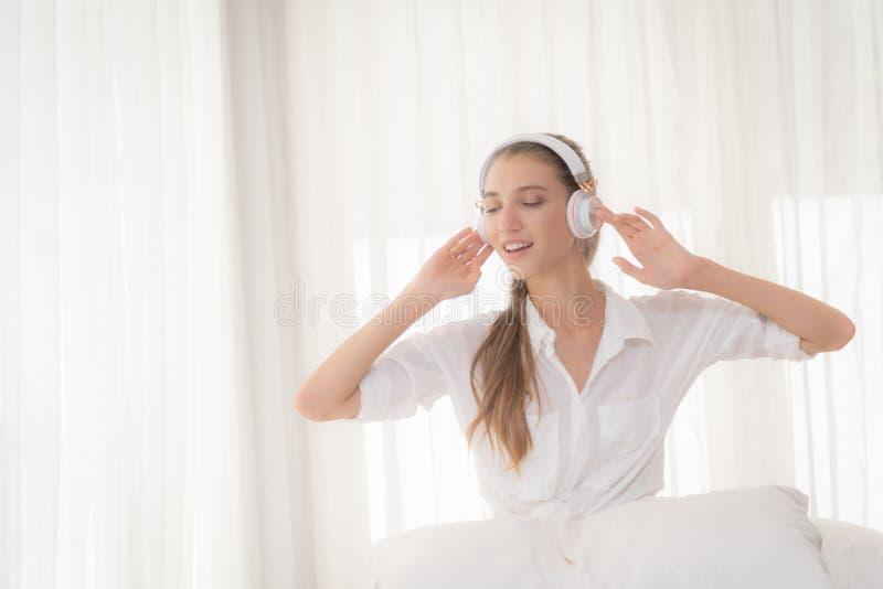 Vrouw ontspannen die aan muziek met hoofdtelefoons luisteren stock foto