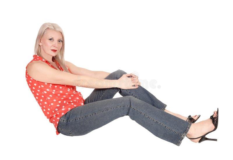 Vrouw ontspannen, die op de vloer in studio zitten royalty-vrije stock foto's