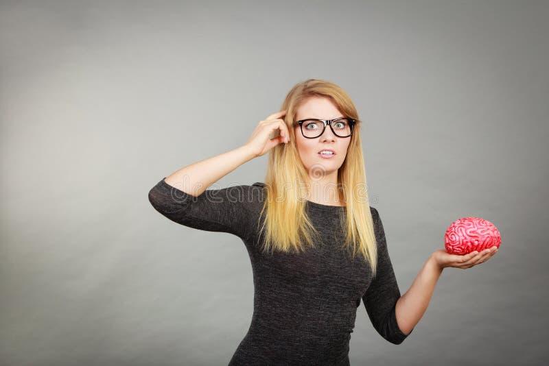 Download Vrouw In Oogglazen Die Verwarde Holdingshersenen Zijn Stock Foto - Afbeelding bestaande uit intellect, vrouw: 107700720