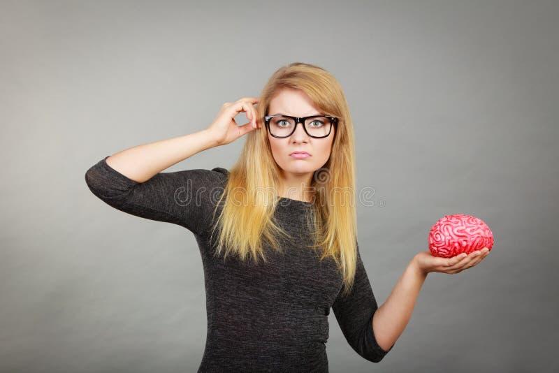 Vrouw in oogglazen die verwarde holdingshersenen zijn stock foto