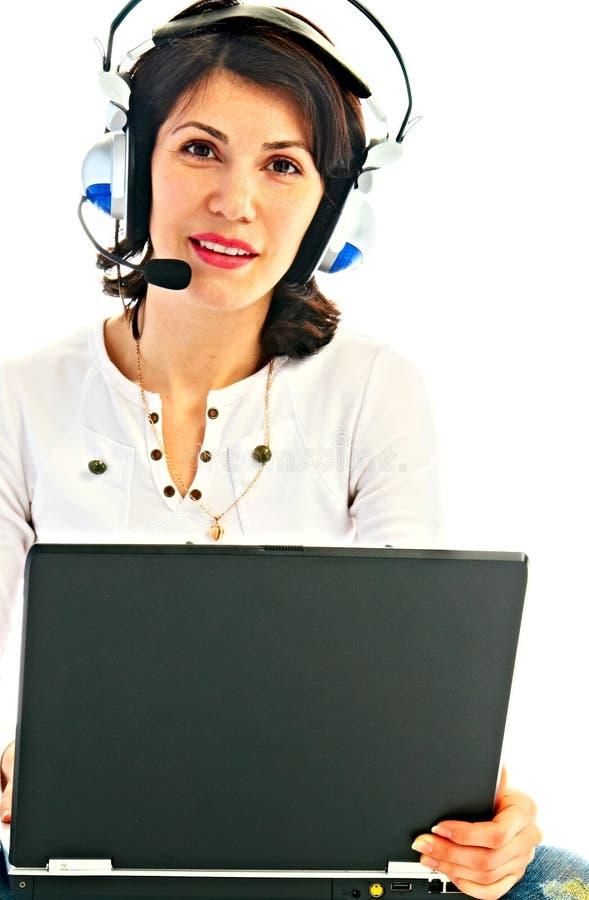 Vrouw in oortelefoon met laptop royalty-vrije stock foto