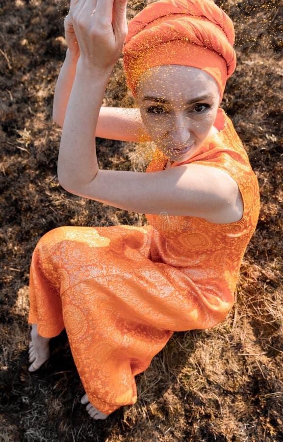 Vrouw in Oostelijke Kleding Bestrooit zich met Gouden Lovertjes Emotionele Portret stock foto's
