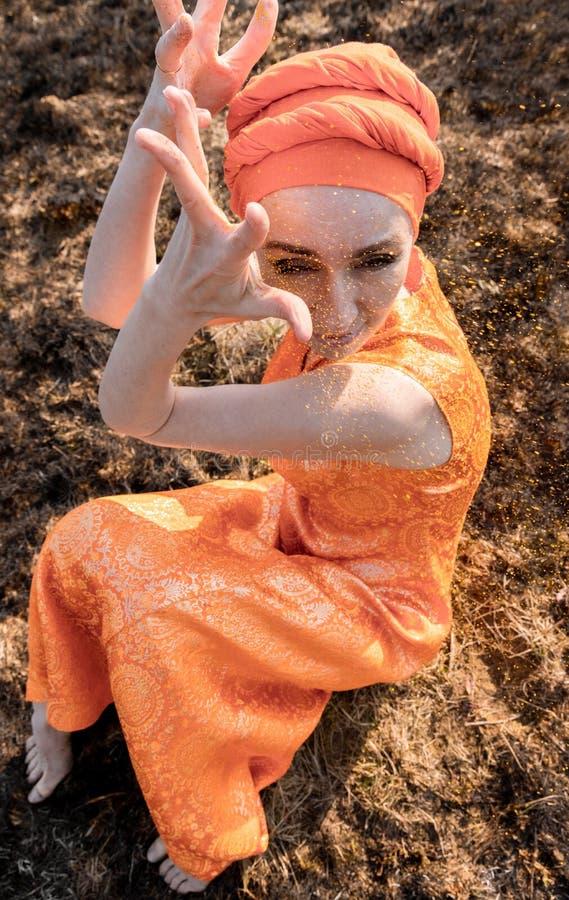 Vrouw in Oostelijke Kleding Bestrooit zich met Gouden Lovertjes Emotionele Portret royalty-vrije stock foto's
