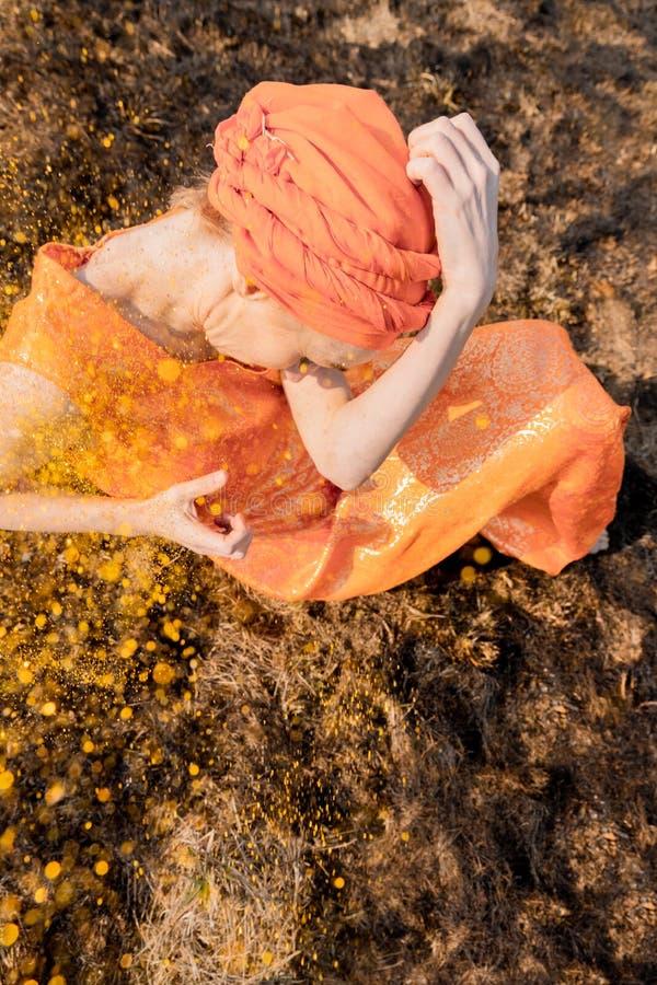 Vrouw in Oostelijke Kleding Bestrooit zich met Gouden Lovertjes Emotionele Portret stock fotografie