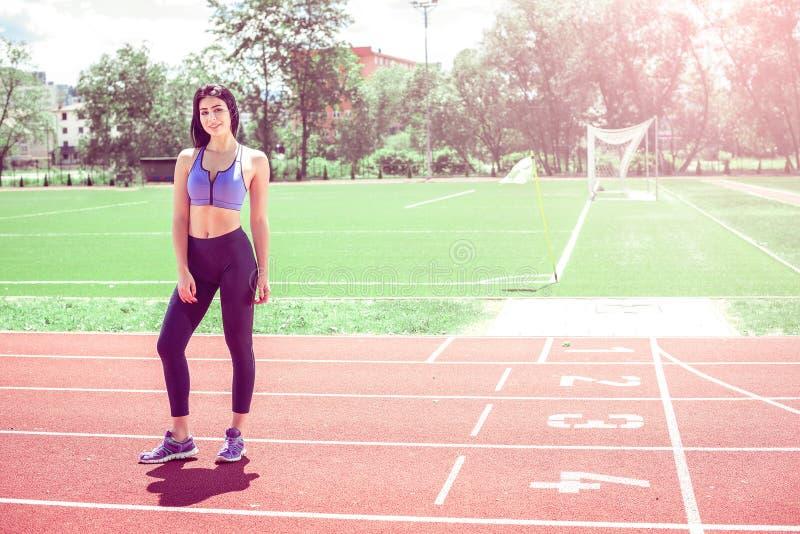 Vrouw op atletische renbaan stock foto's