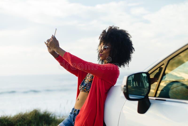 Vrouw op autoreis die foto met mobiele telefoon nemen tegen het overzees stock foto's