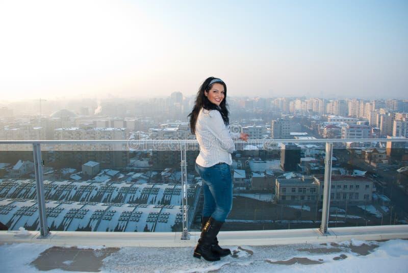 Vrouw op balkon met stadsmening stock foto's