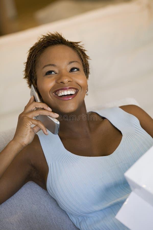 Vrouw op bank die op cel spreekt royalty-vrije stock foto