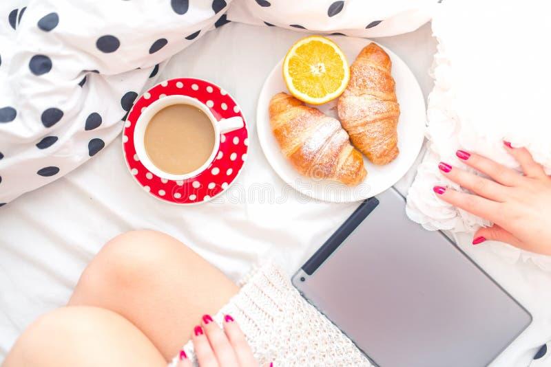 Vrouw op bed met tablet, ontbijt en koffie, die op een zondagochtend ontspannen stock foto's