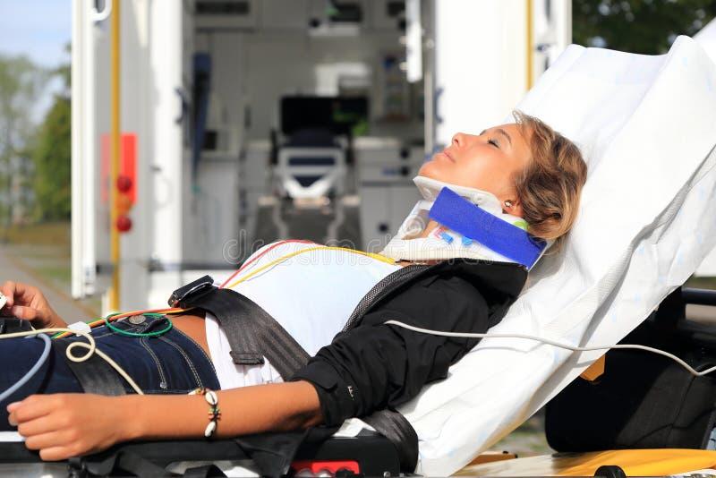 Vrouw op brancard en stifneck vóór Ziekenwagenauto na ongeval stock afbeelding