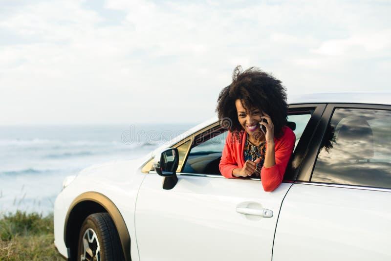 Vrouw op cellphonevraag tijdens autoreis aan de kust stock foto