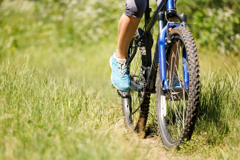Vrouw op de close-up van de bergfiets stock foto