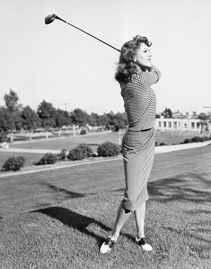 Vrouw op de drijfwaaier die een golfclub slingeren (Alle afgeschilderde personen leven niet langer en geen landgoed bestaat Lever stock fotografie