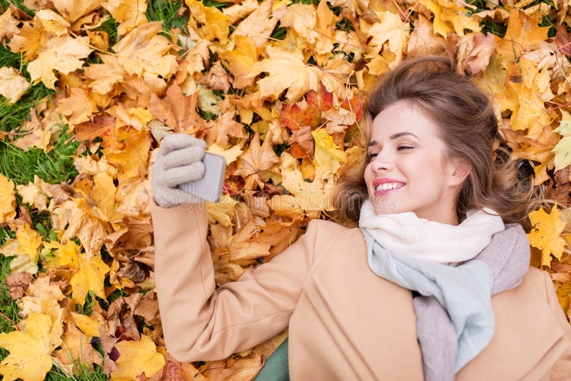 Vrouw op de herfstbladeren die selfie door smartphone nemen stock afbeelding