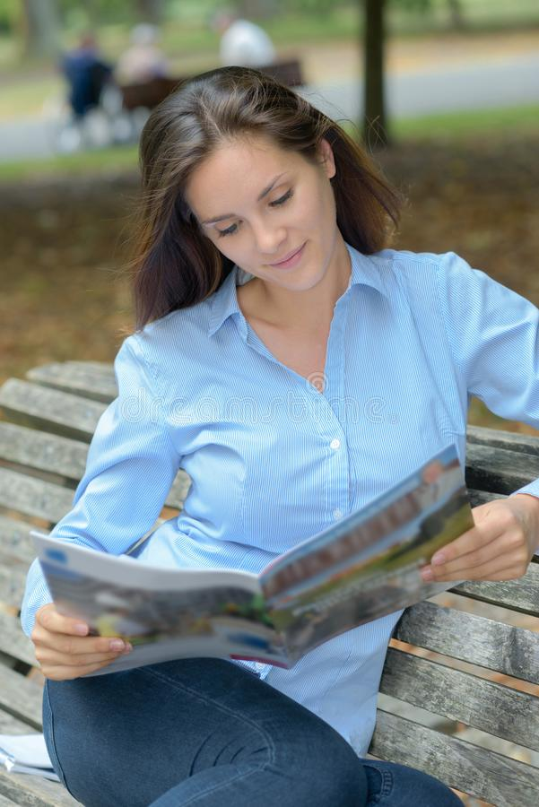 Vrouw op de lezingstijdschrift van de parkbank royalty-vrije stock foto