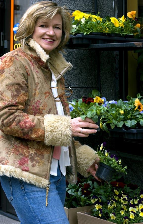 Vrouw op de straat met bloemen stock fotografie