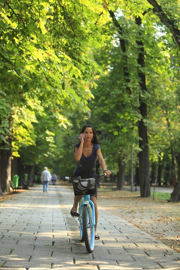 Vrouw op de telefoon berijdende fiets stock foto's