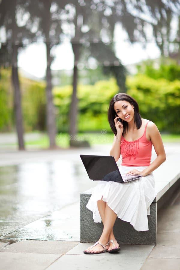 Vrouw op de telefoon en het werken aan haar laptop stock foto's