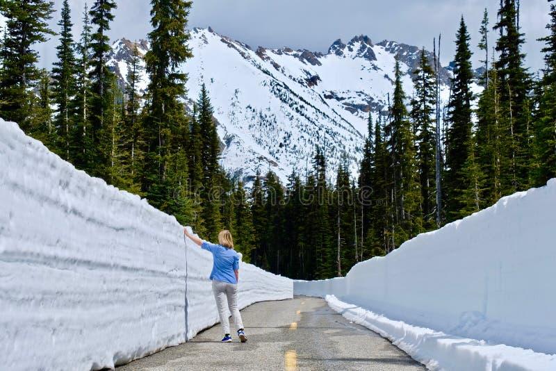 Vrouw op de weg met sneeuwmuren royalty-vrije stock fotografie