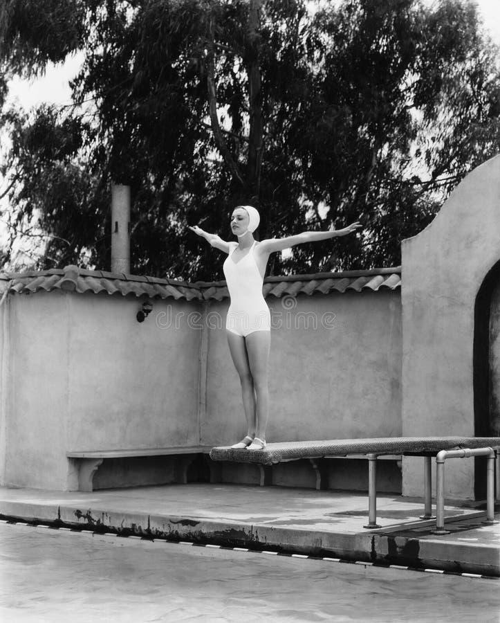 Vrouw op duikplank bij zwembad (Alle afgeschilderde personen leven niet langer en geen landgoed bestaat Leveranciersgaranties dat royalty-vrije stock fotografie