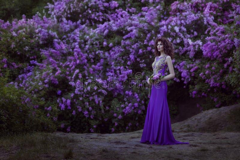 Vrouw op een achtergrond van bloeiende lilac bloemen royalty-vrije stock fotografie