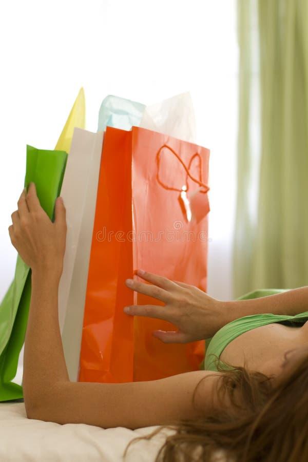 Vrouw op een bed met drie kleuren het winkelen zakken stock fotografie