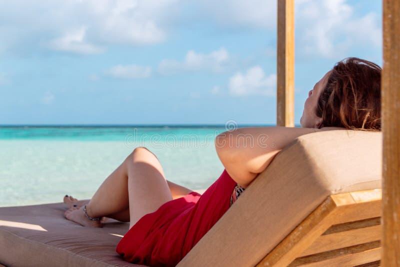 Vrouw op een en sunchair die de idyllische mening in een tropische plaats ontspannen kijken Duidelijk turkoois water als achtergr royalty-vrije stock foto