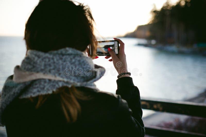 Vrouw op een koude die dag in een sjaal op het strand wordt verpakt stock afbeelding