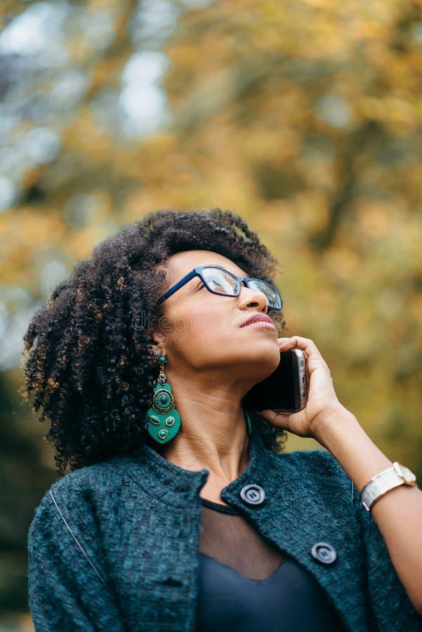 Vrouw op een mobiel telefoongesprek in de herfst royalty-vrije stock foto