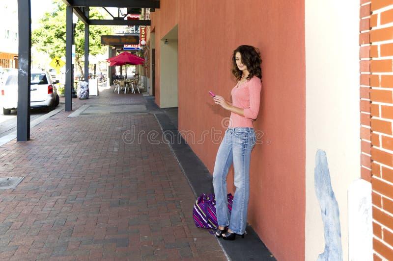 Vrouw op een stoep die een cellphone gebruiken stock foto's