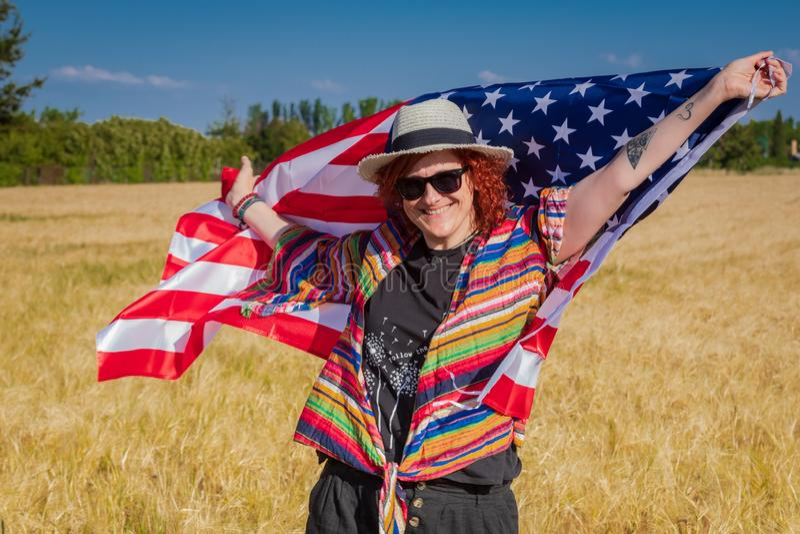 Vrouw op een tarwegebied met een vlag van de V.S. stock afbeeldingen