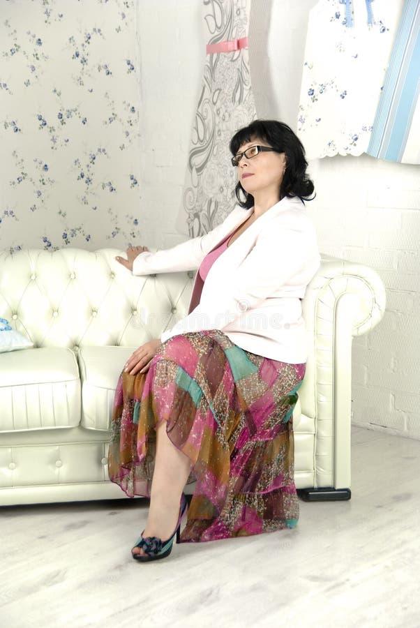 Vrouw op een witte bank royalty-vrije stock foto's